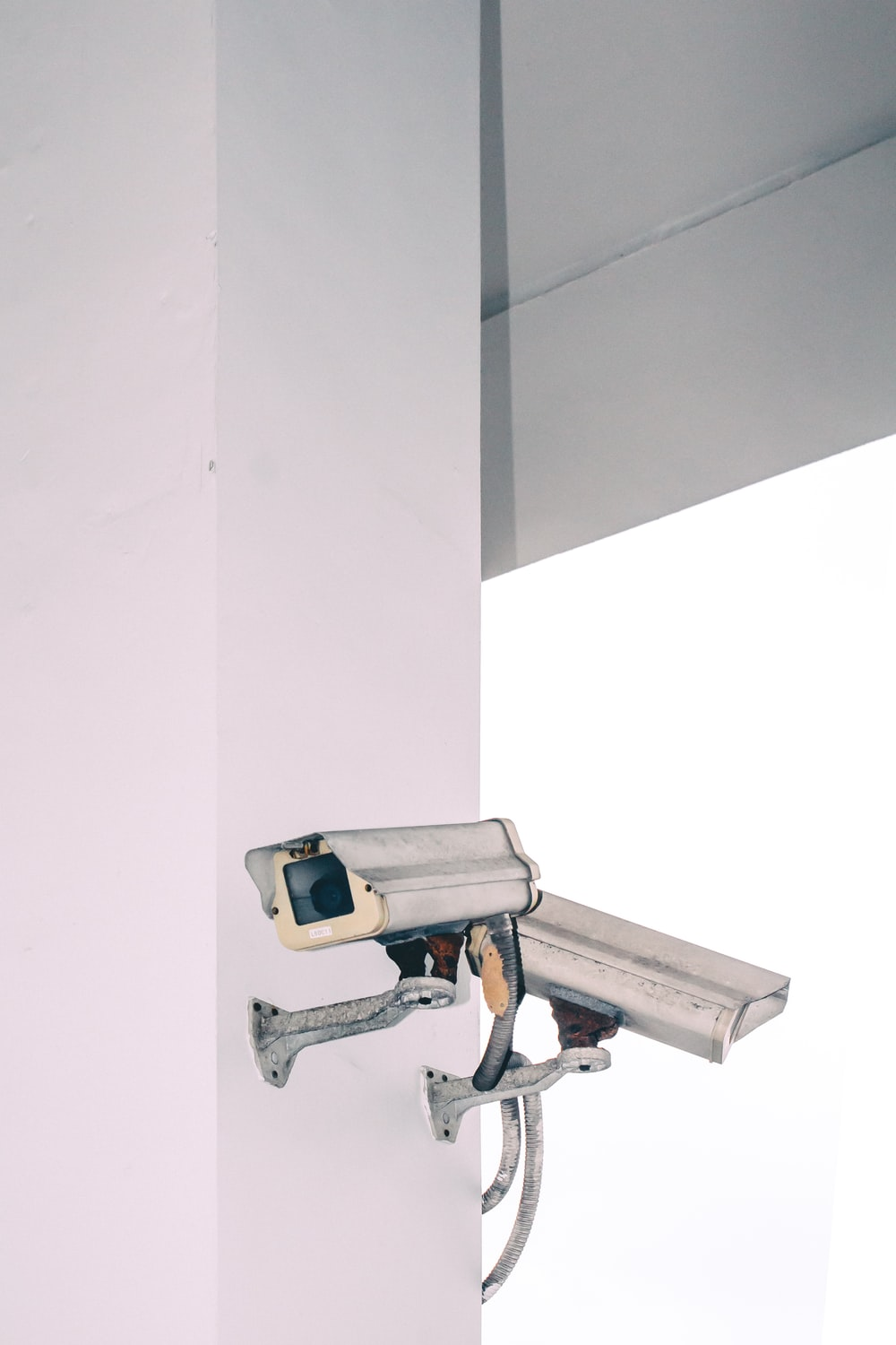 two bullet security camera attached on wall