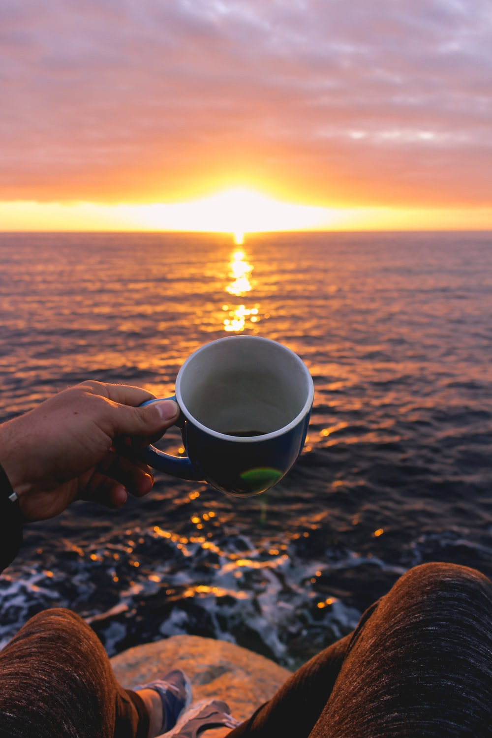person holding blue cup looking at sunset
