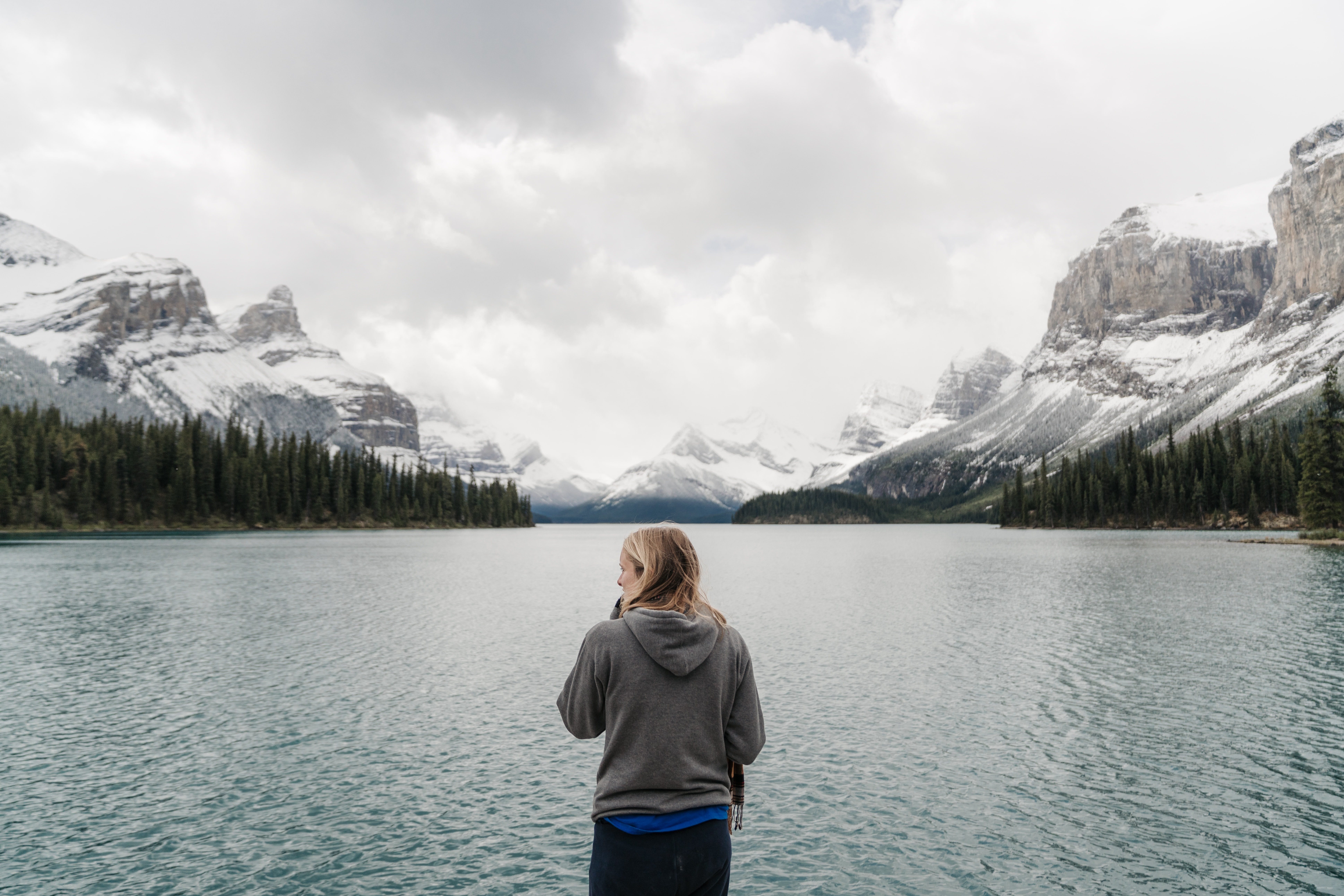 woman standing in front of lake and mountains