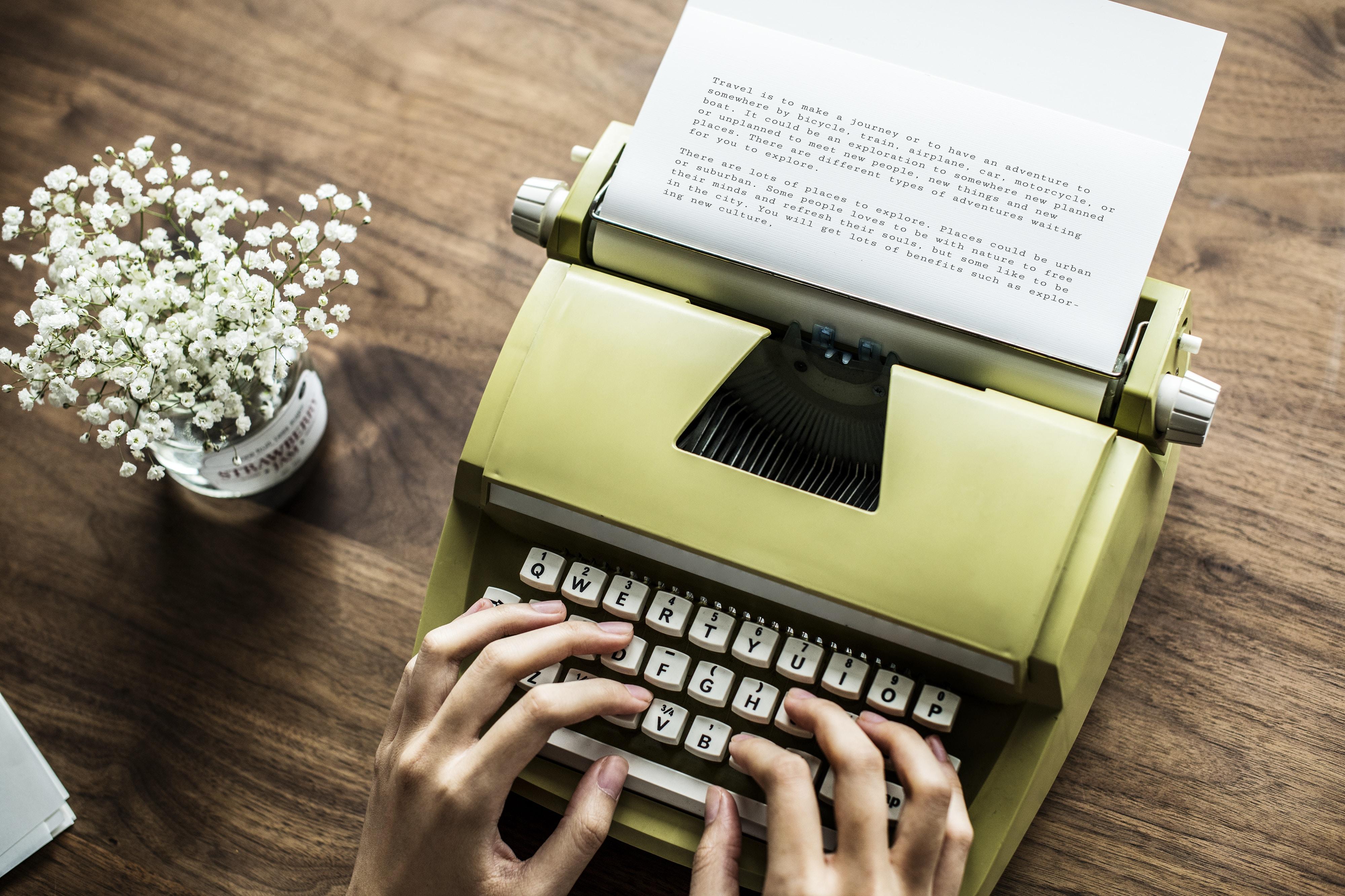 person typing on brown typewriter