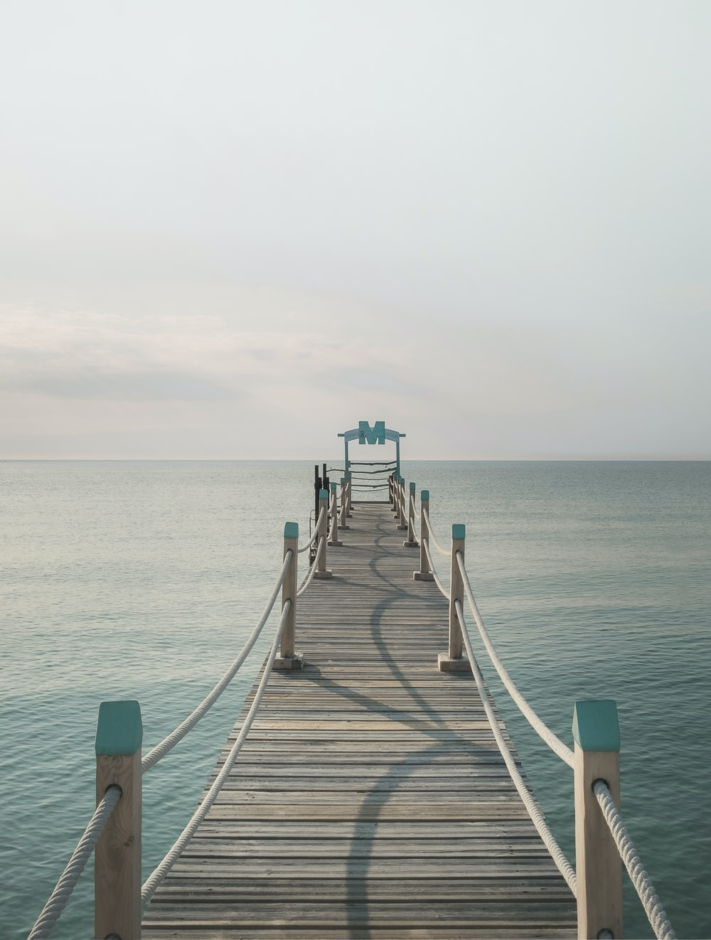 brown wooden pier near body of calm water