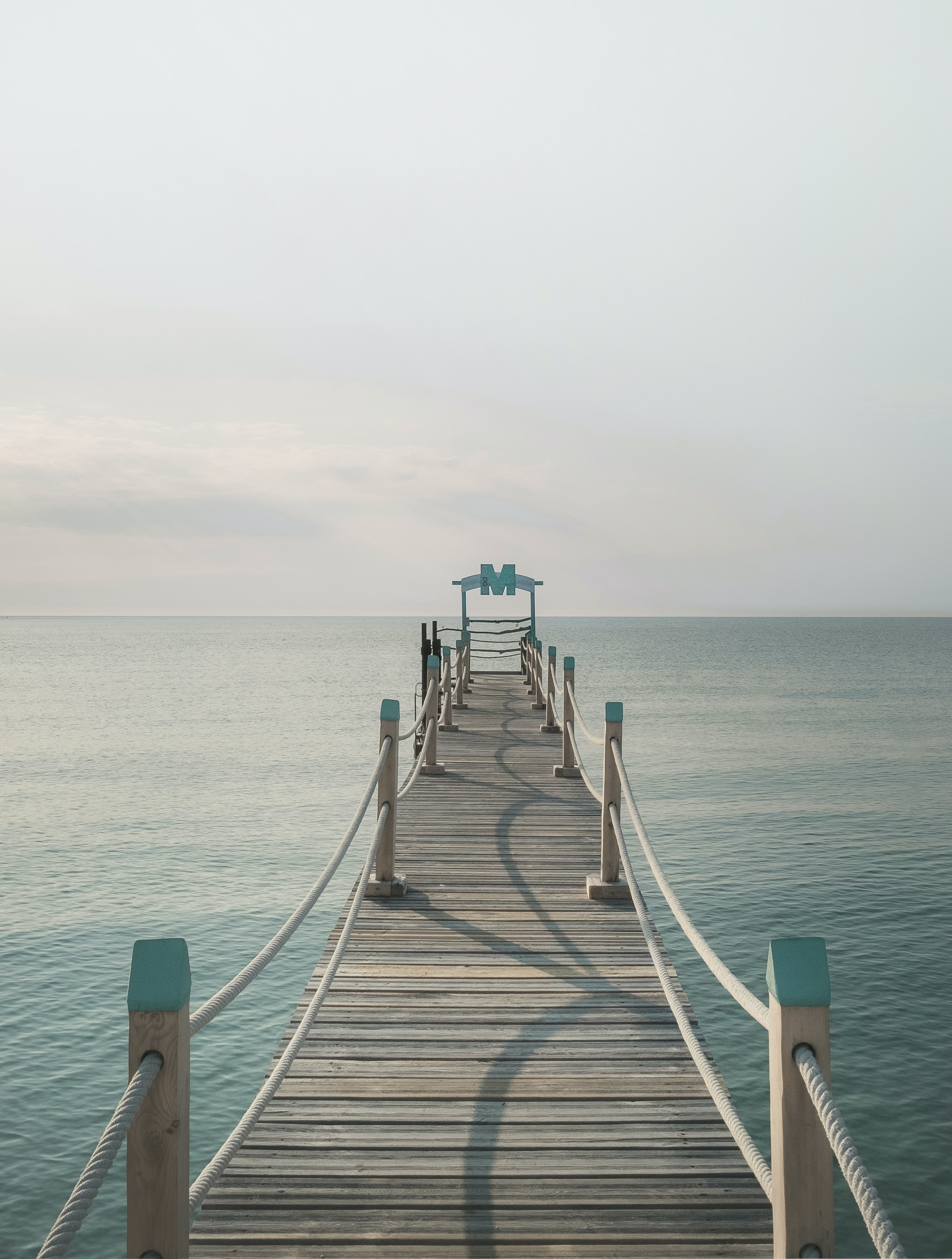 brown wooden pier near body of calm water