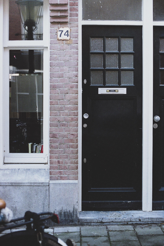 black door beside brown wall