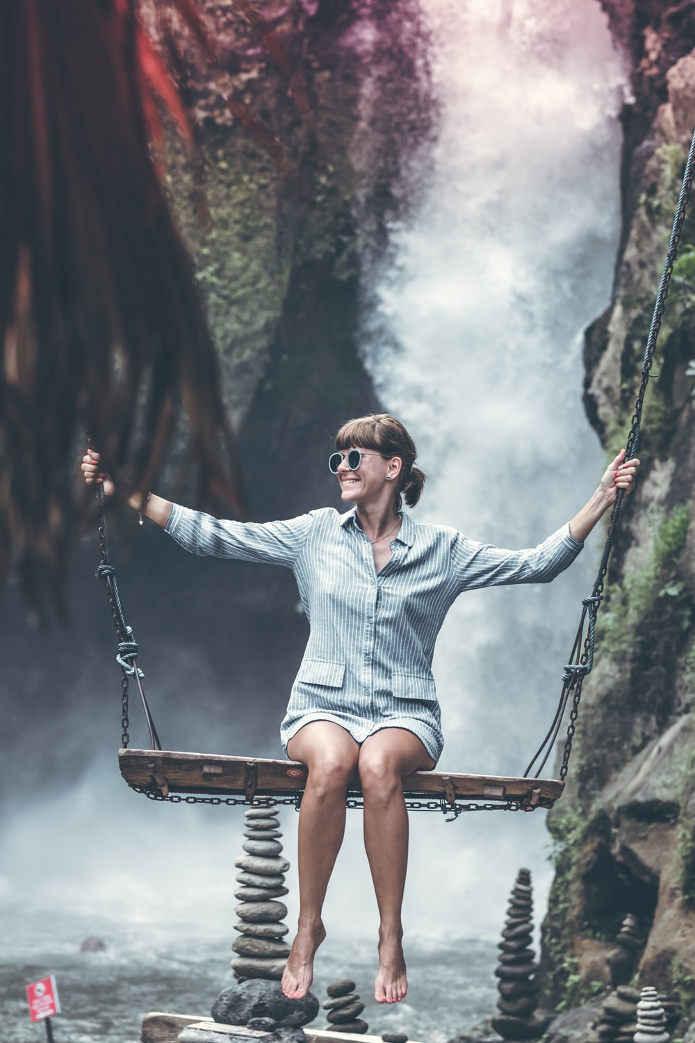 woman sitting on brown wooden swing