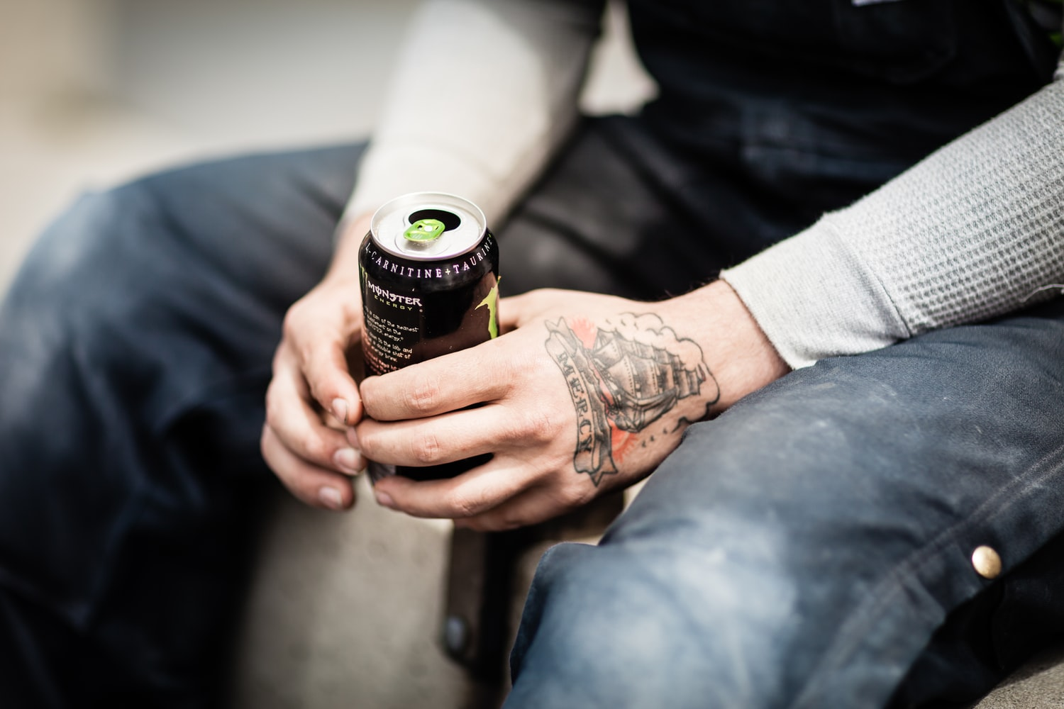 sitting tattooed person holding a can of energy drink