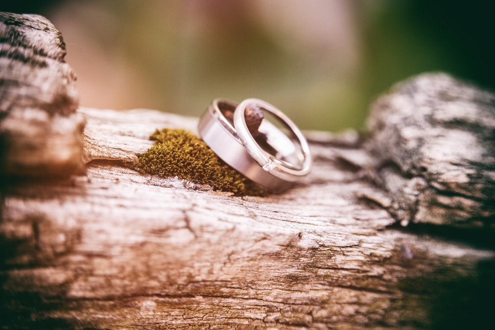 two silver-colored wedding bands on gray wood