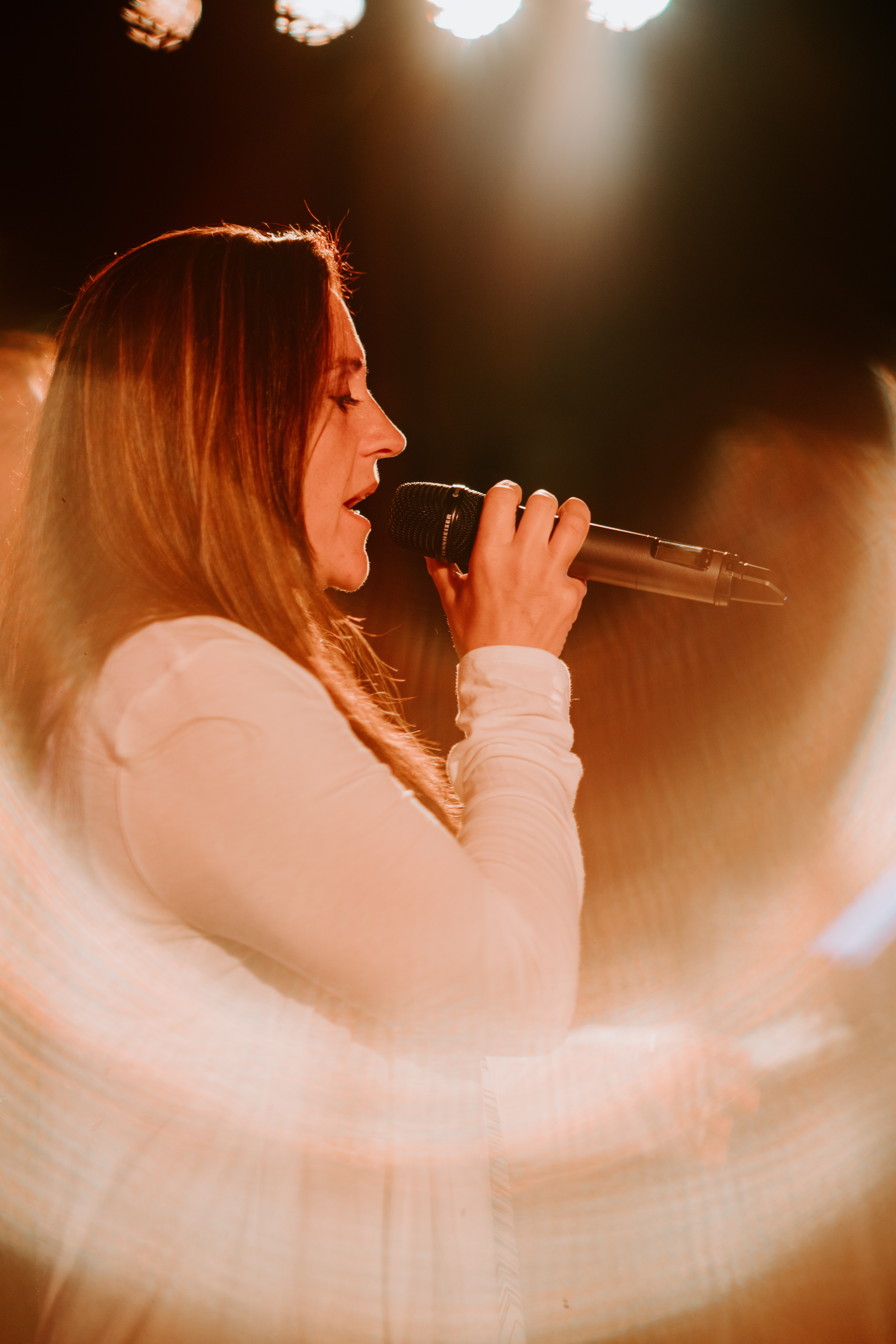 woman holding microphone while singing on stage