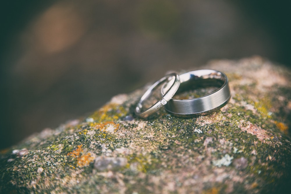 two silver-colored rings on stone