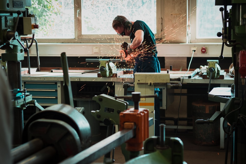 selective focus photography of man using angle grinder