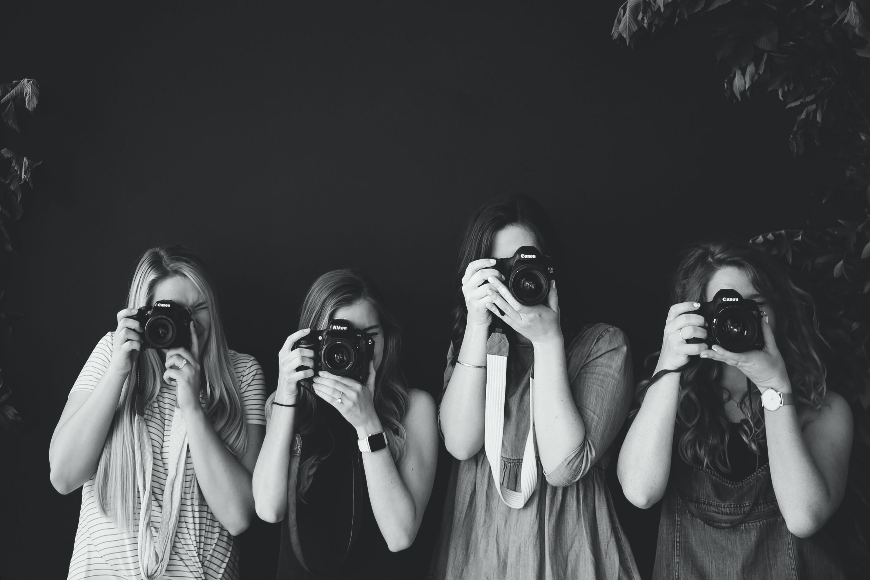 grayscale photography of four women taking photos