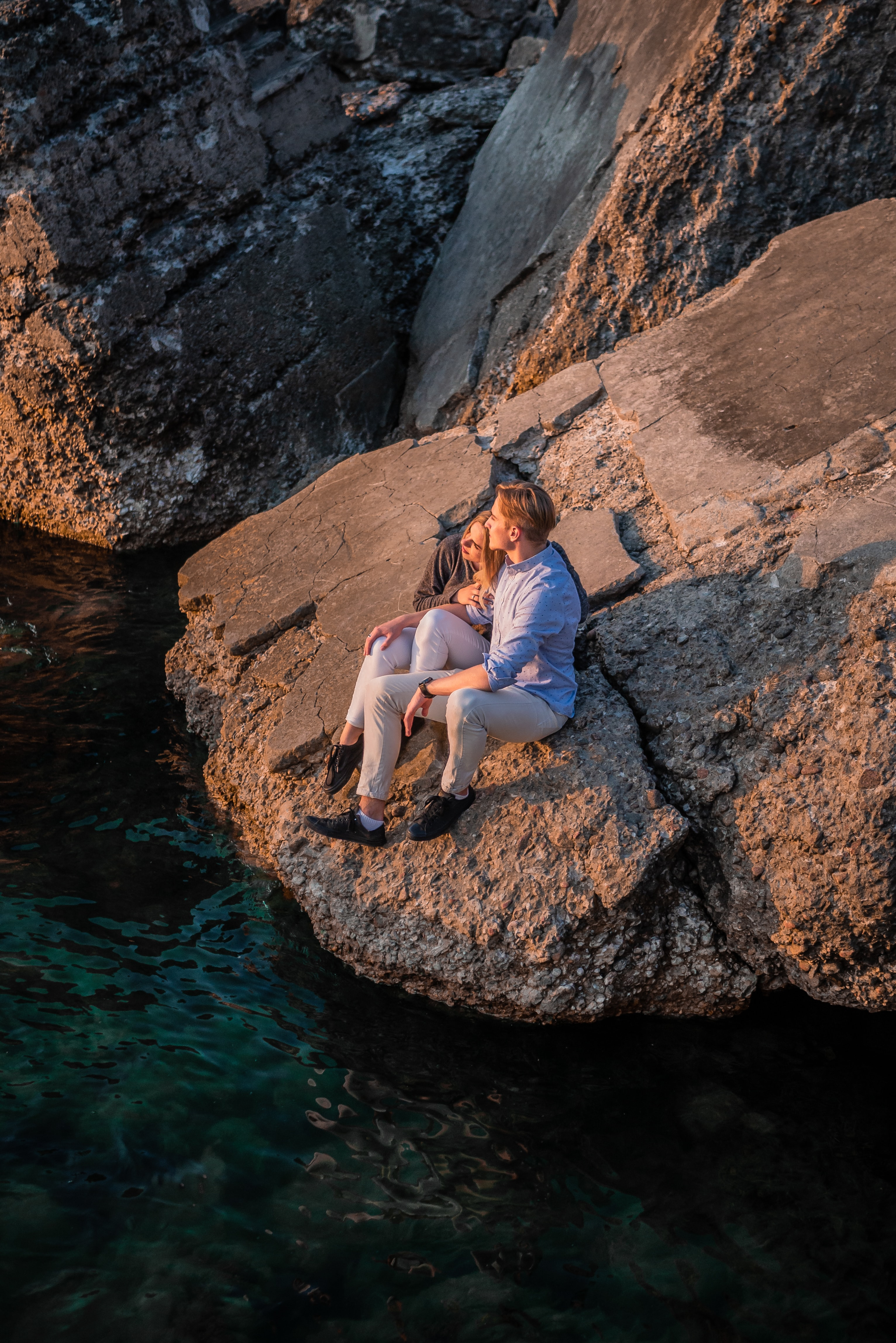 man and woman sitting on rock near body of water during daytime