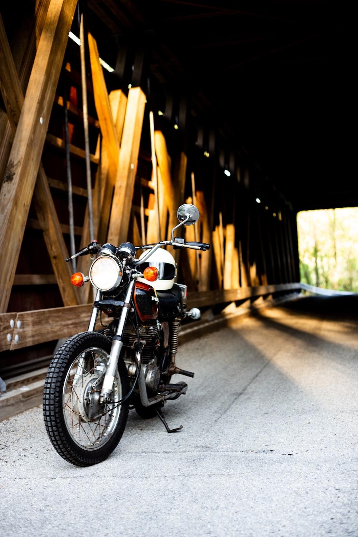 black motorcycle near brown wooden tunnel bridge