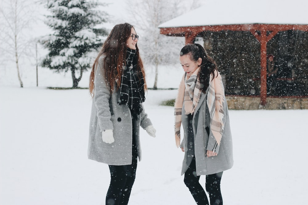 two woman standing on snow field