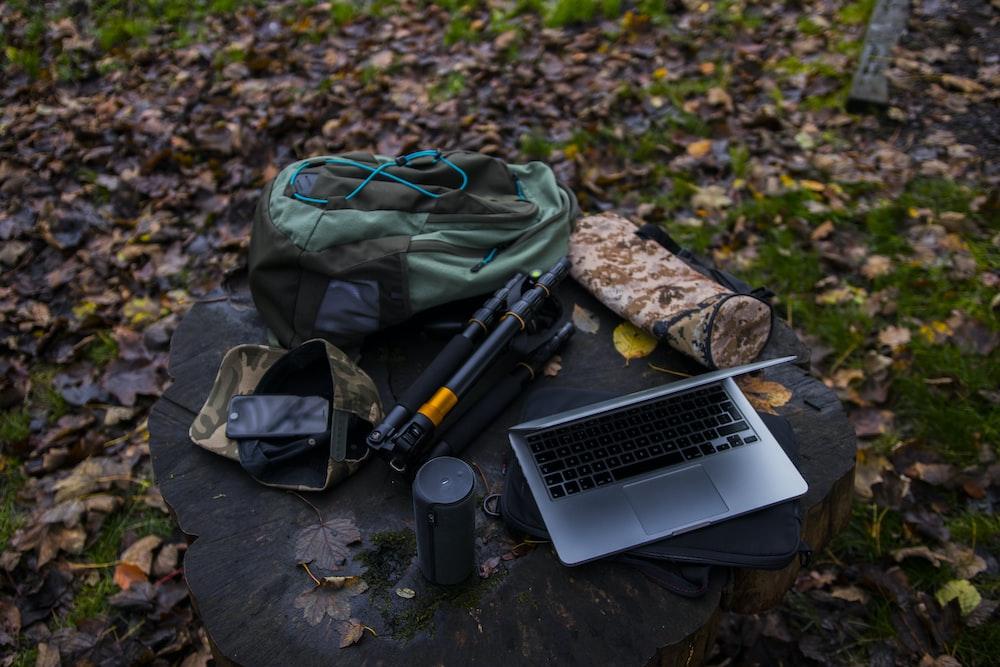 silver laptop, bag, and tripod at stump