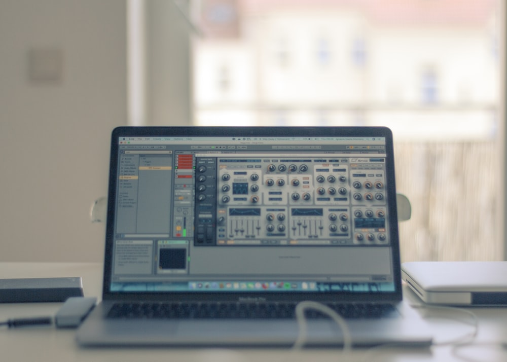 turned-on MacBook Pro on white table near window