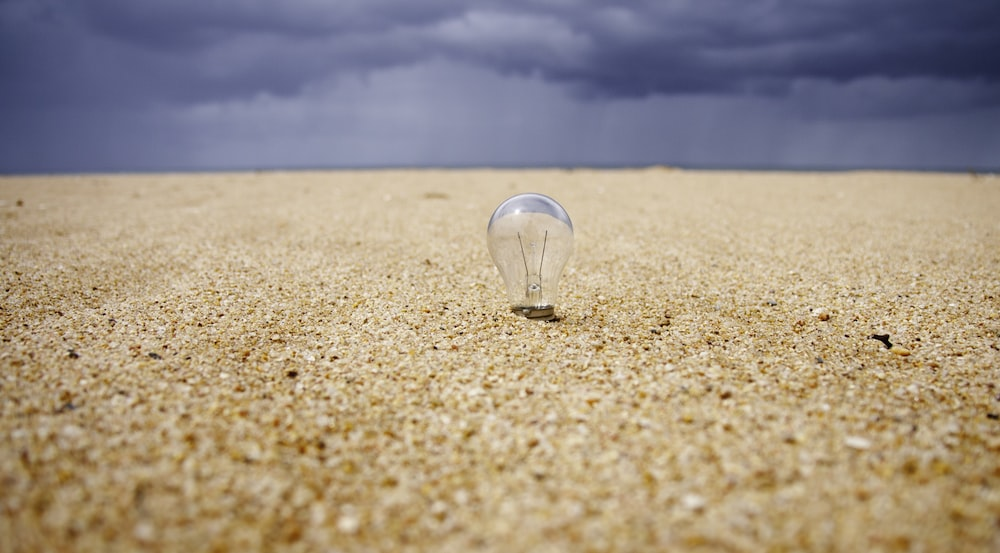close up photography of LED bulb on sand