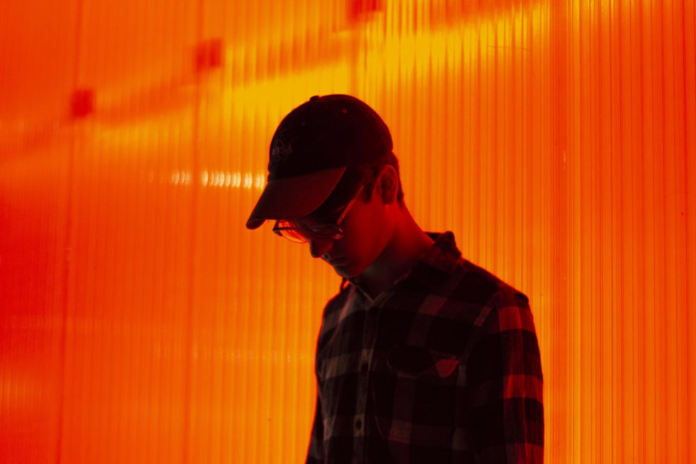 person wearing cap standing on orange wall