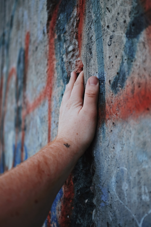 left human hand touching gray wall