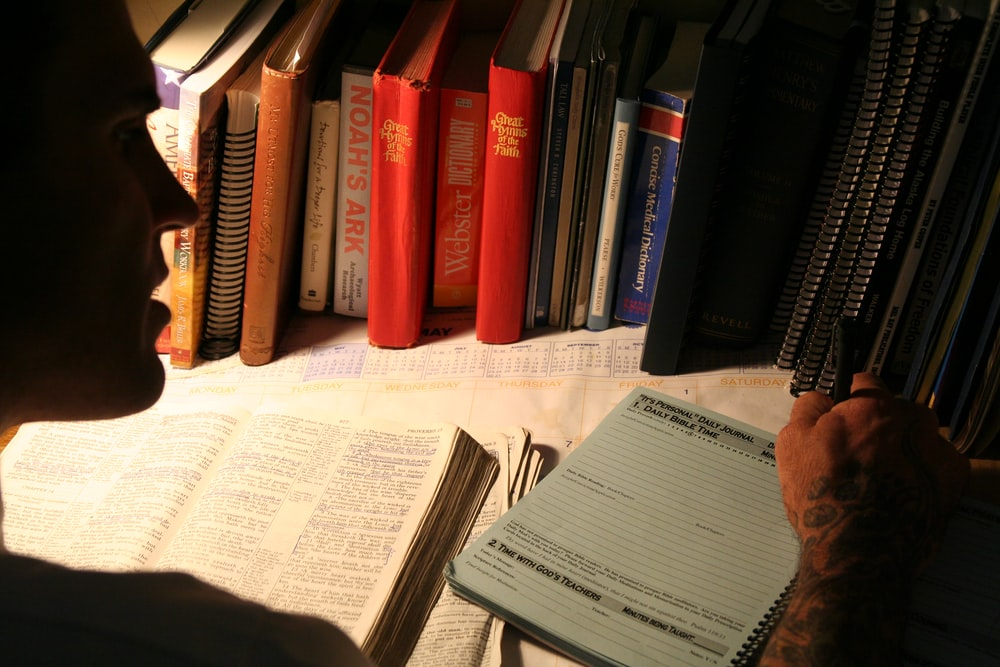 man writing in front of books