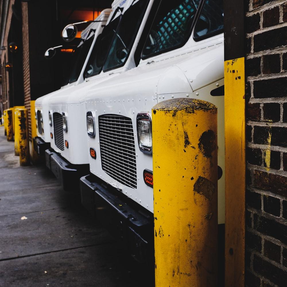 three white vehicle parked on garage