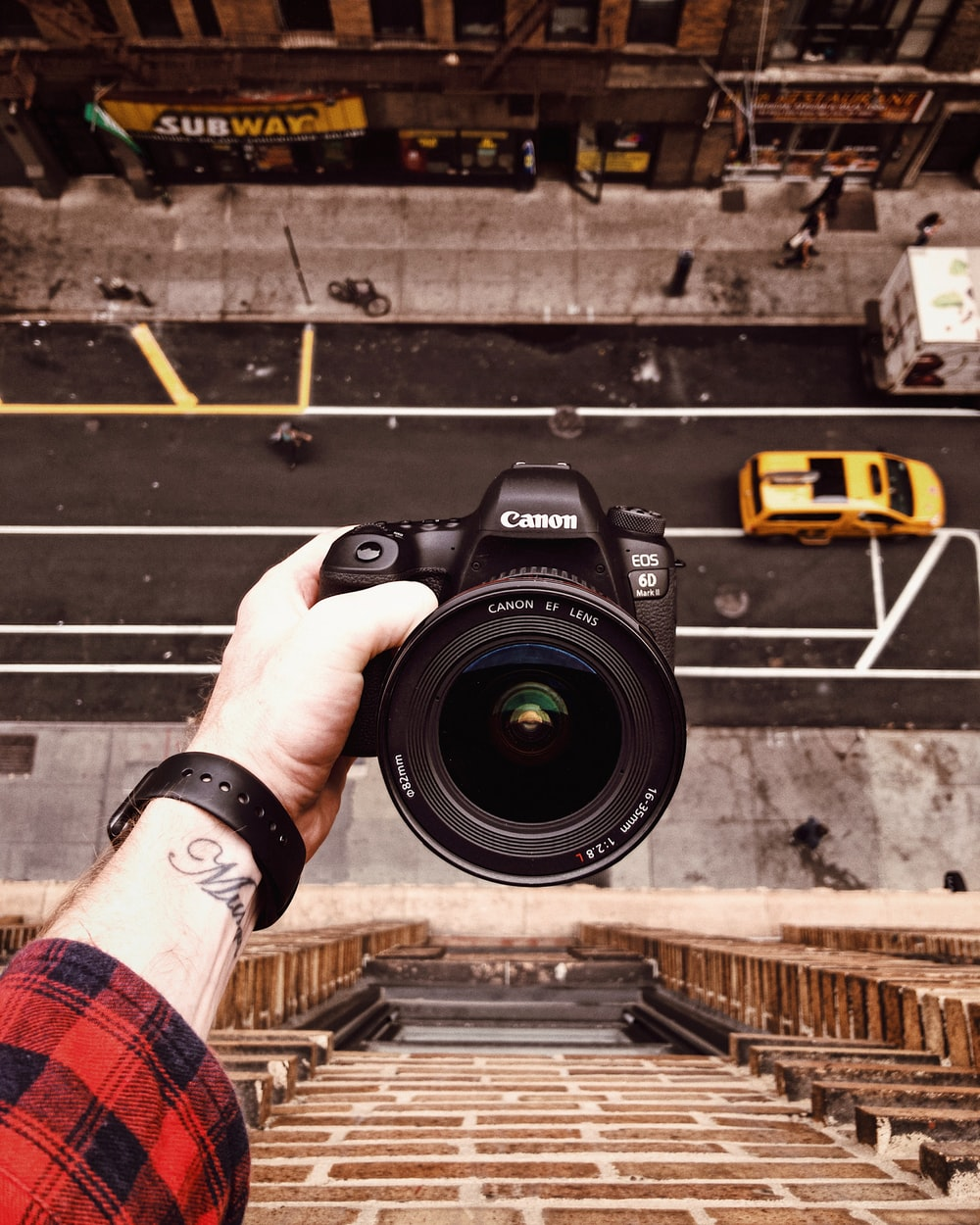 person holding black Canon EOS 6D outside window