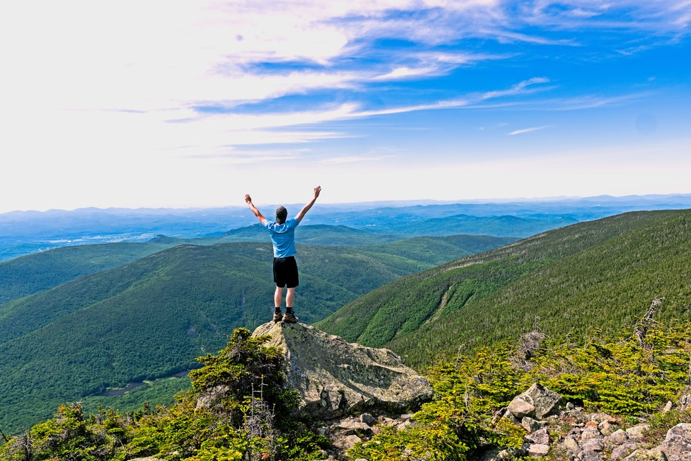man raising his hands standing on mountain range