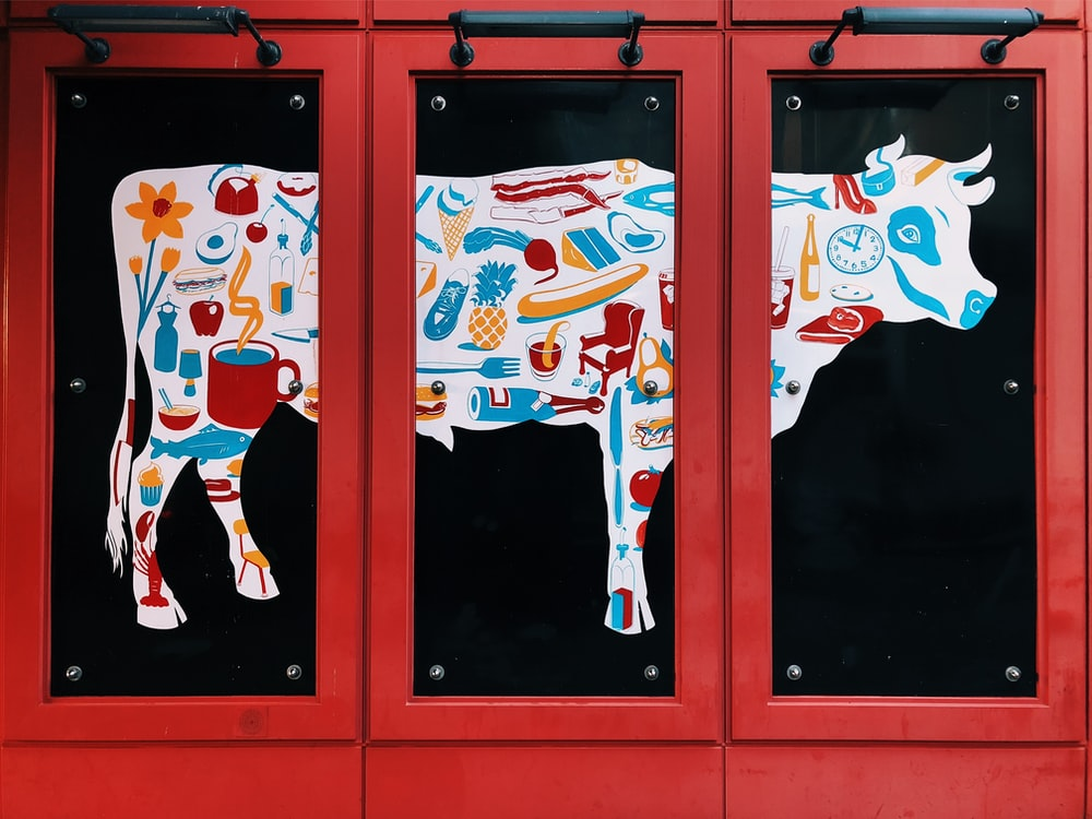 white, blue, and red cow 3-panel painting on wall