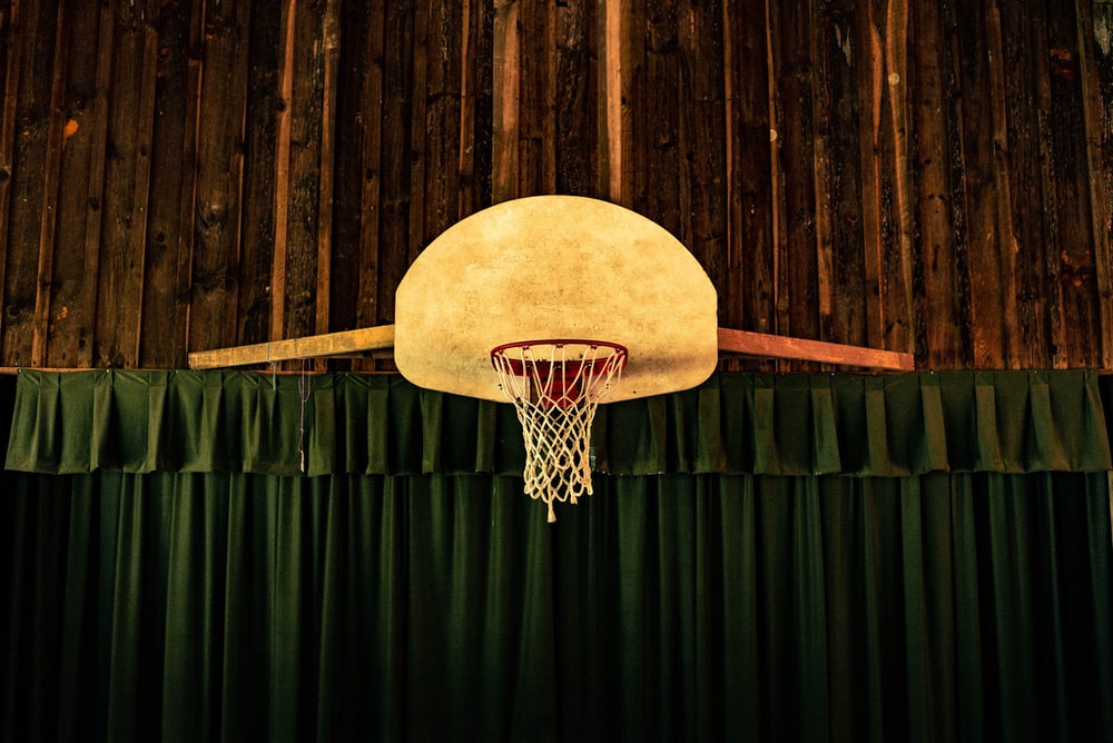 brown and red basketball hoop near green curtains