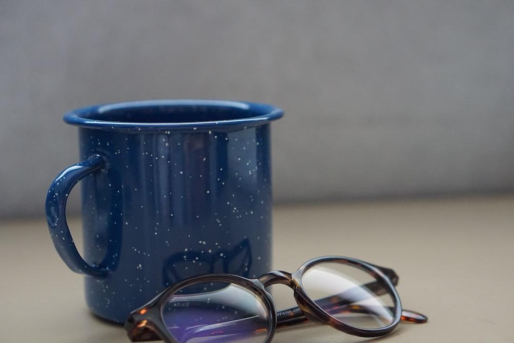 black metal mug beside eyeglasses