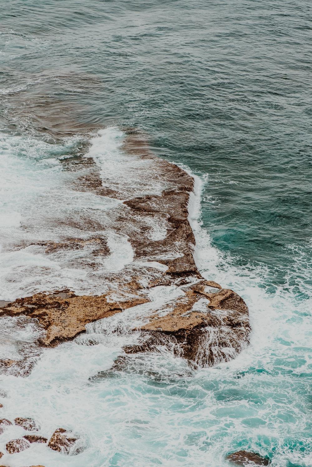 rock formation beside body of water