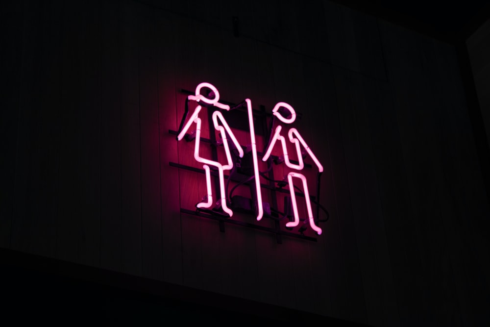 man and woman neon signage at dark area
