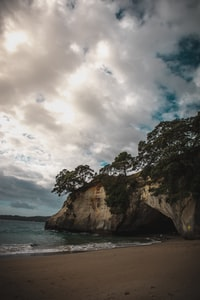 rock formation surrounded by trees near body of water under cloudy sky at daytime