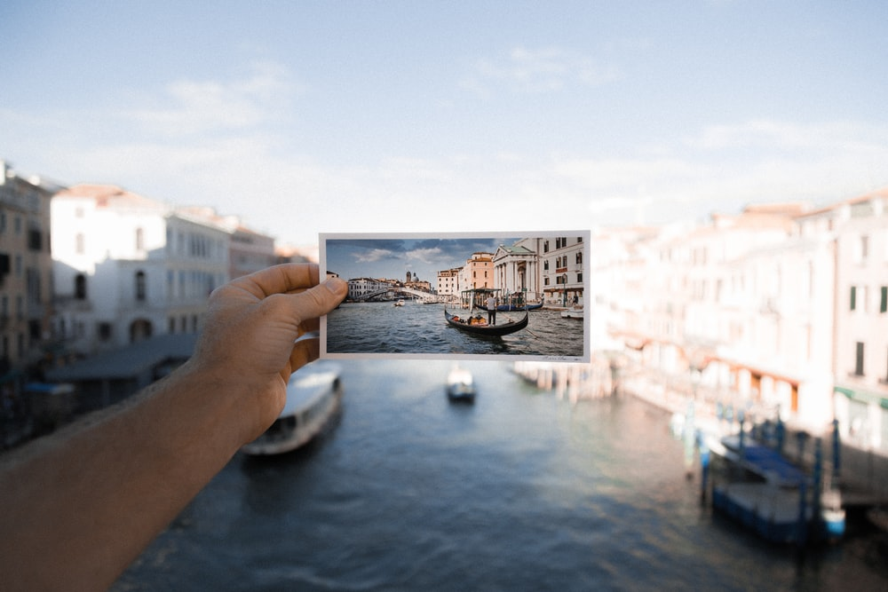 person holding photo of boat on body of water