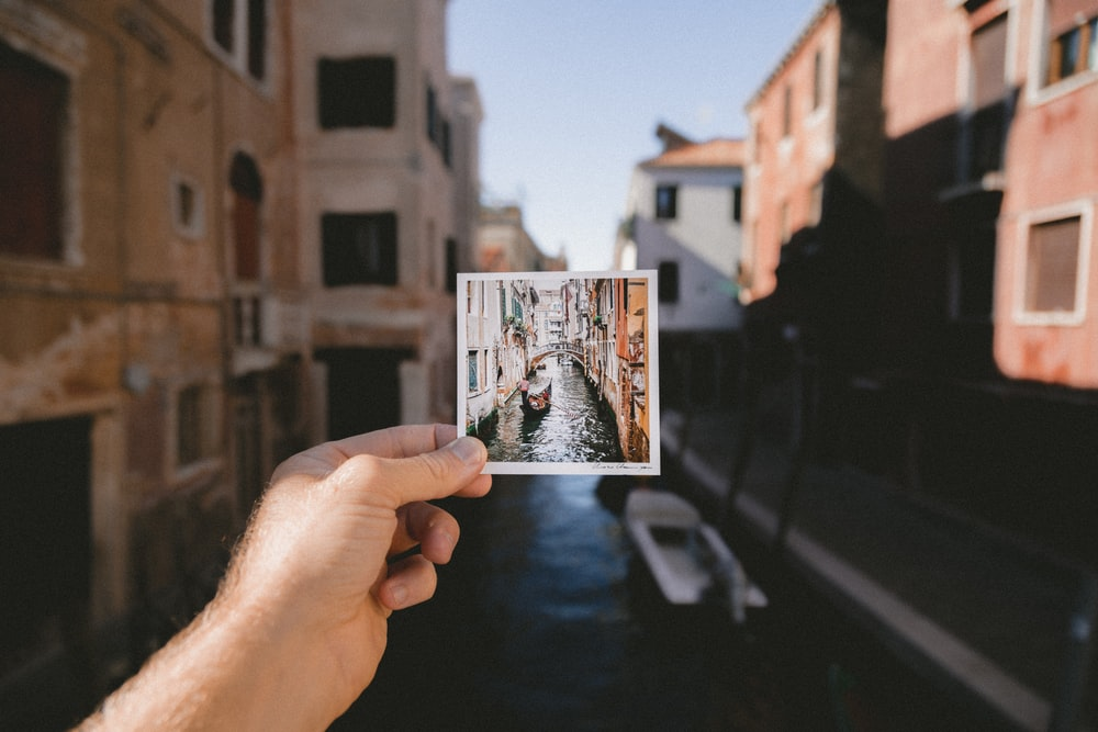 person holding photo of grand canal