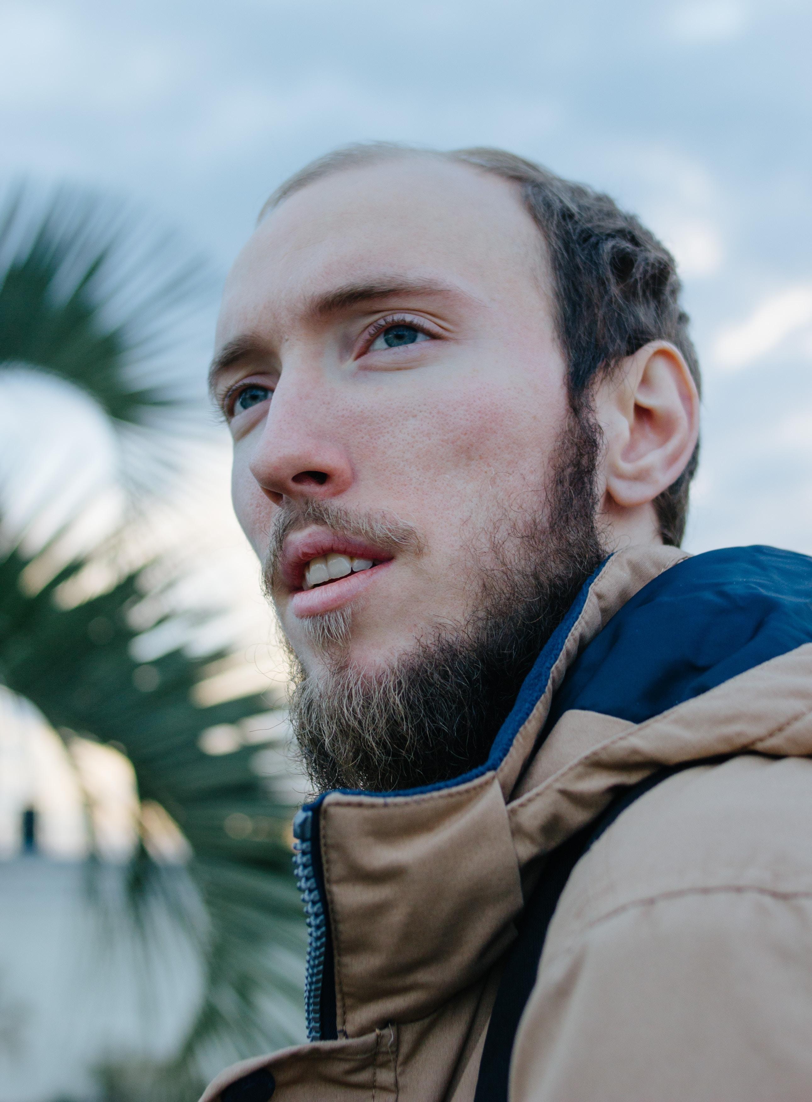 man wearing blue jacket looking in distance