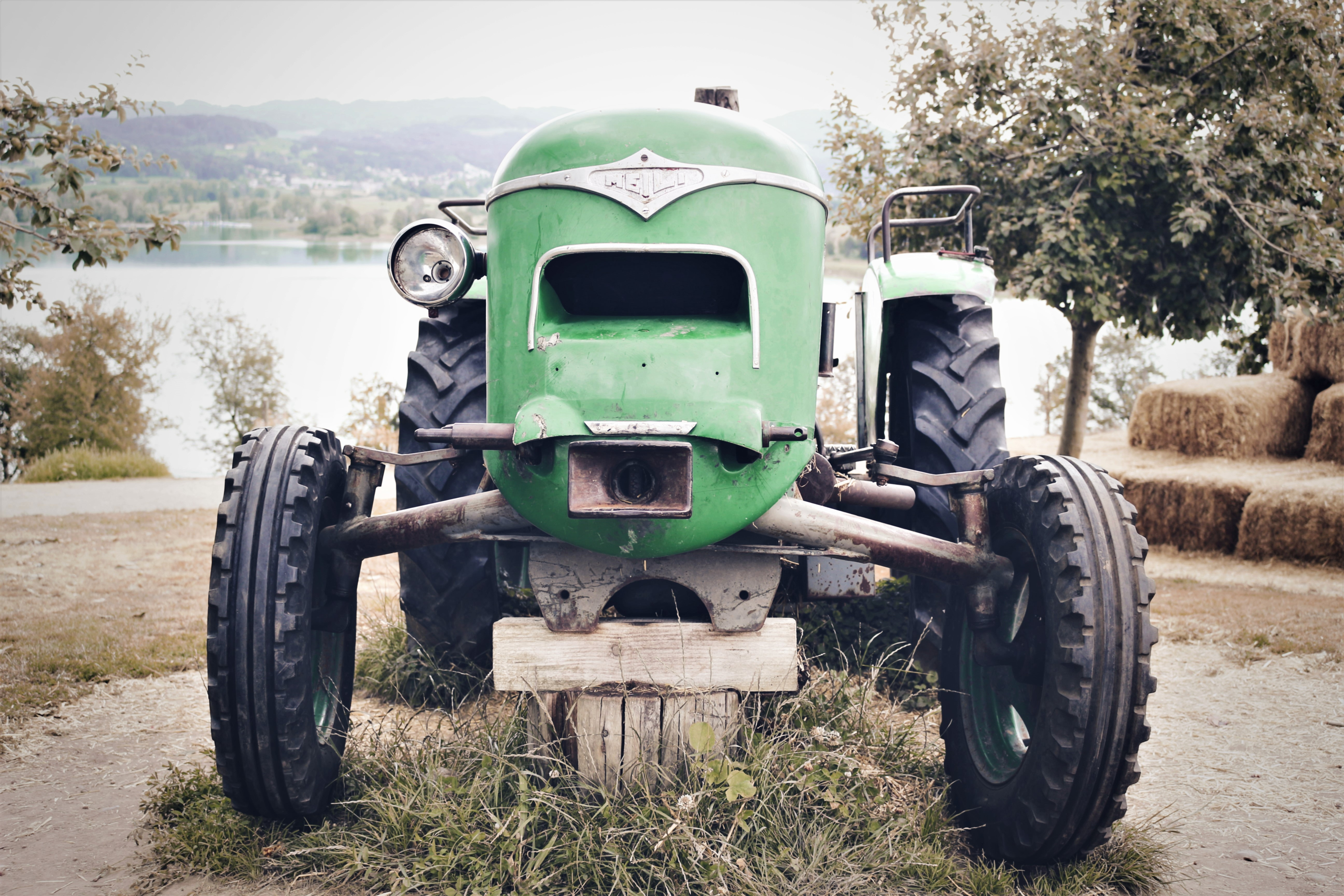 selective focus photography of green tractor near body of water