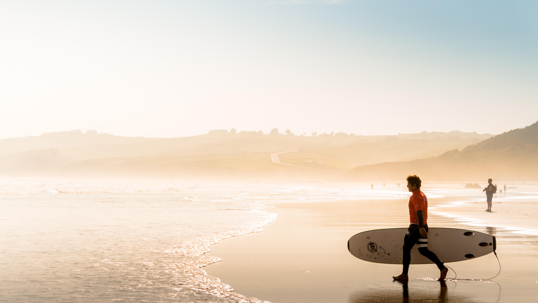 man holding surfboard on seashore