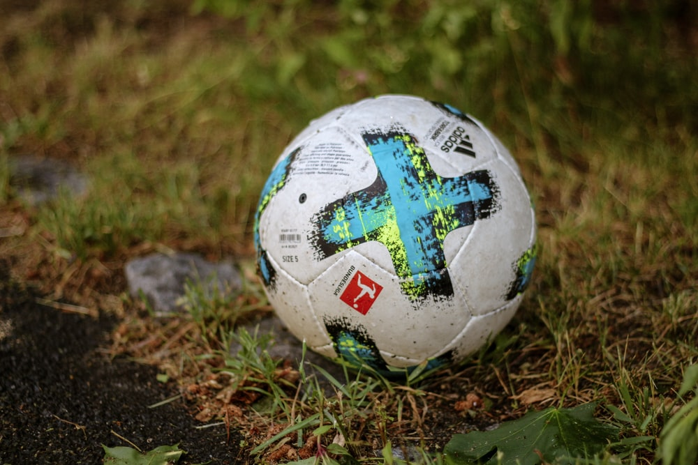white and teal soccer ball on green grass