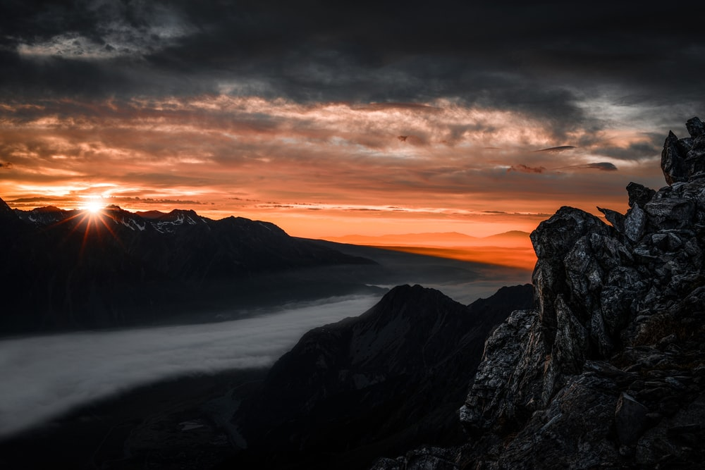 high angle photography of mountain range under nimbus clouds