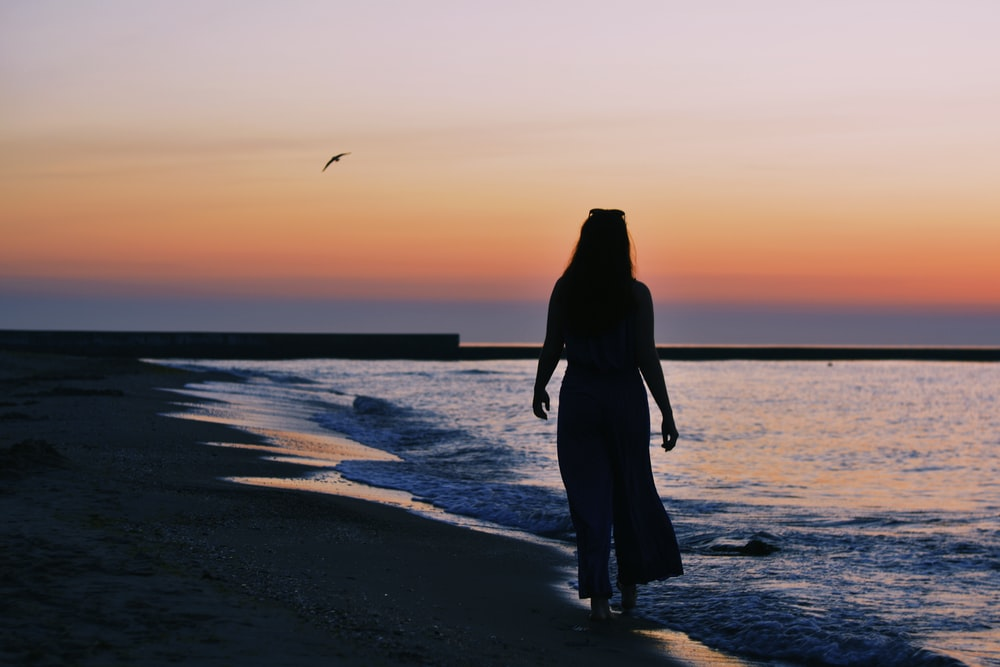 woman silhouette on beach shore during golden hour