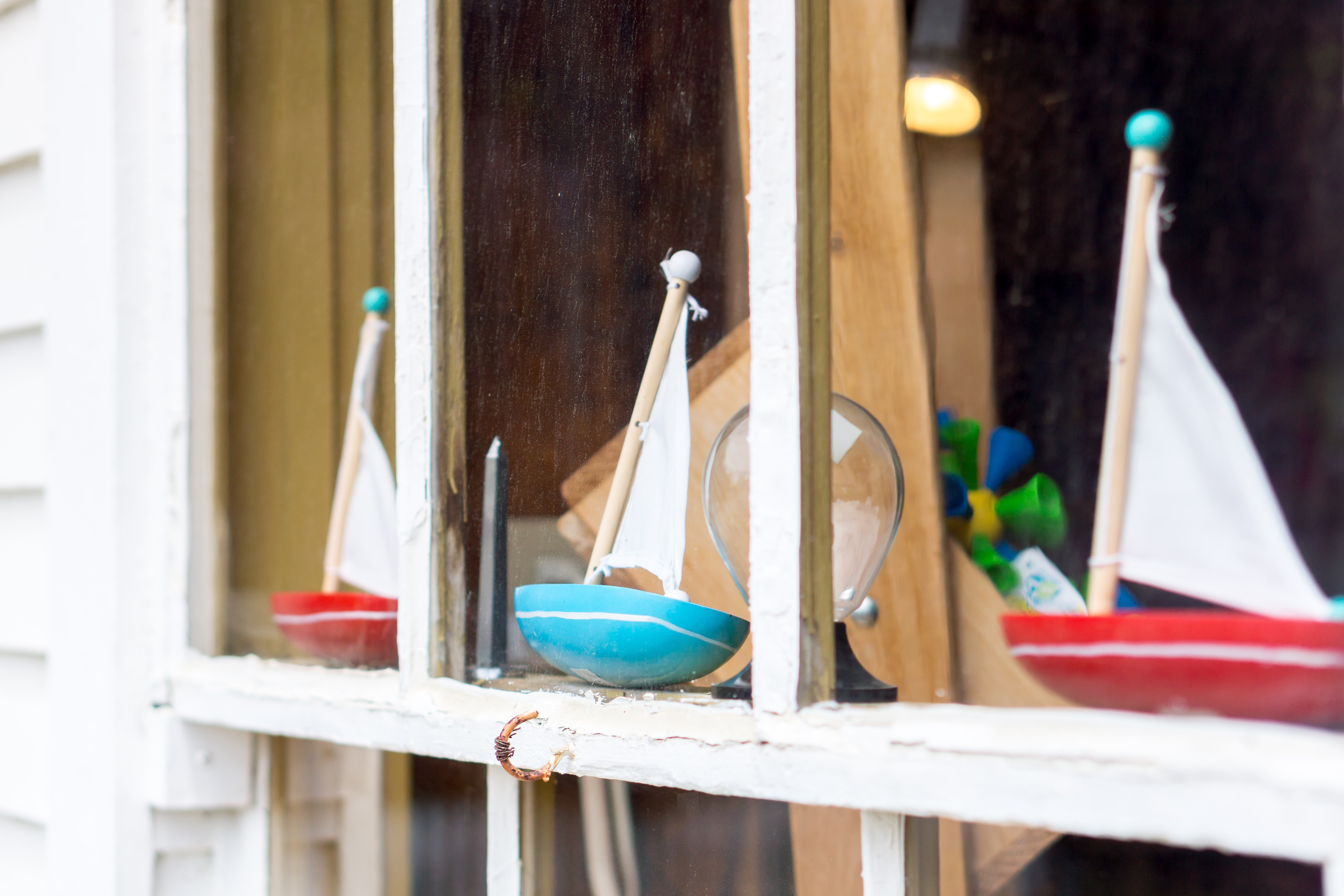 two red and one teal sailboat toys