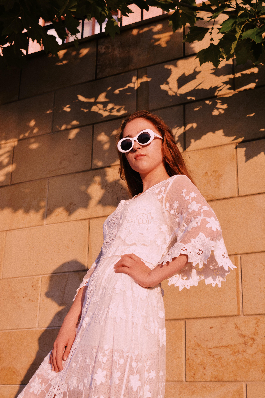 woman wearing white lace dress standing beside wall