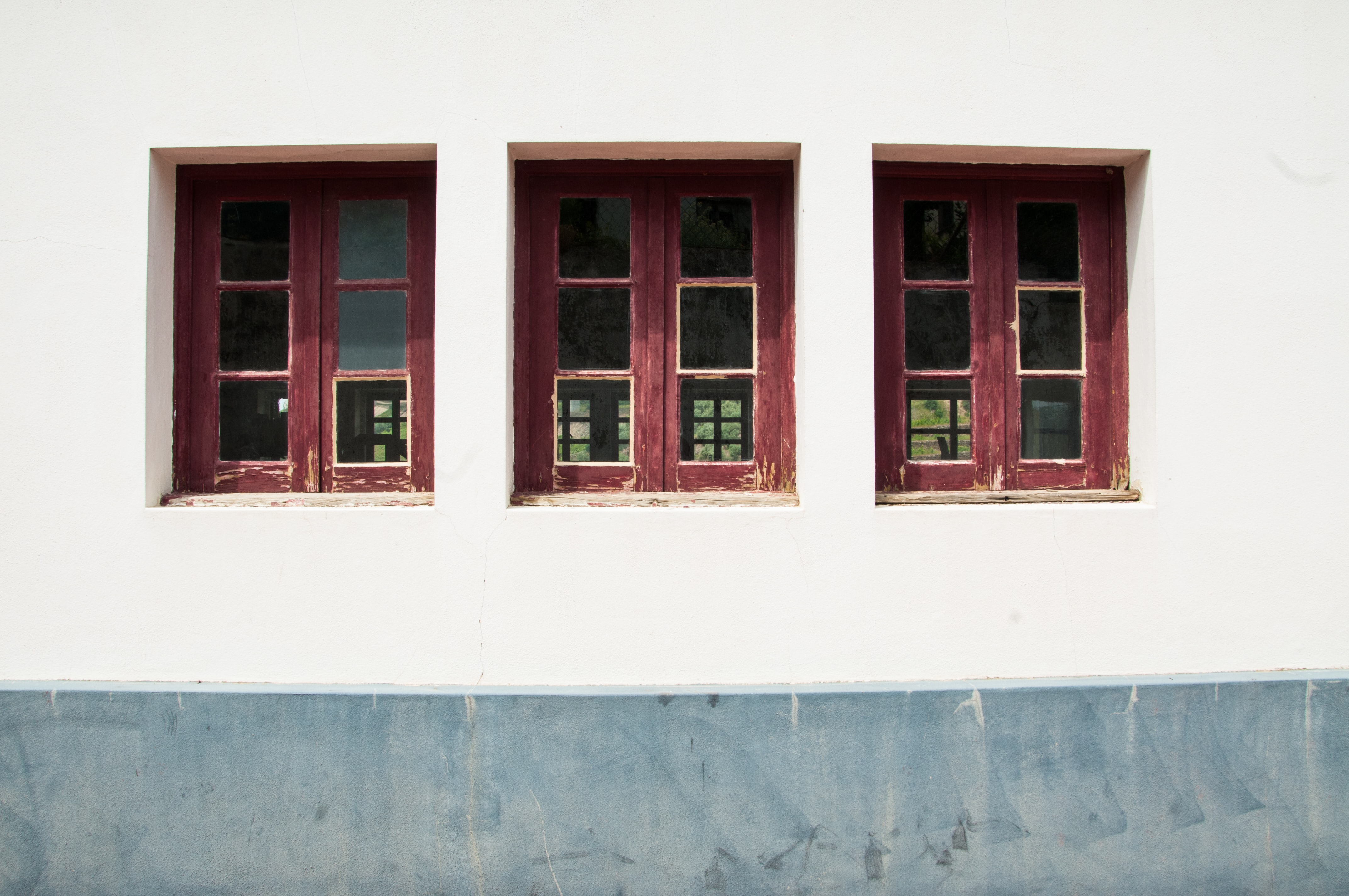 three closed red windows on white wall