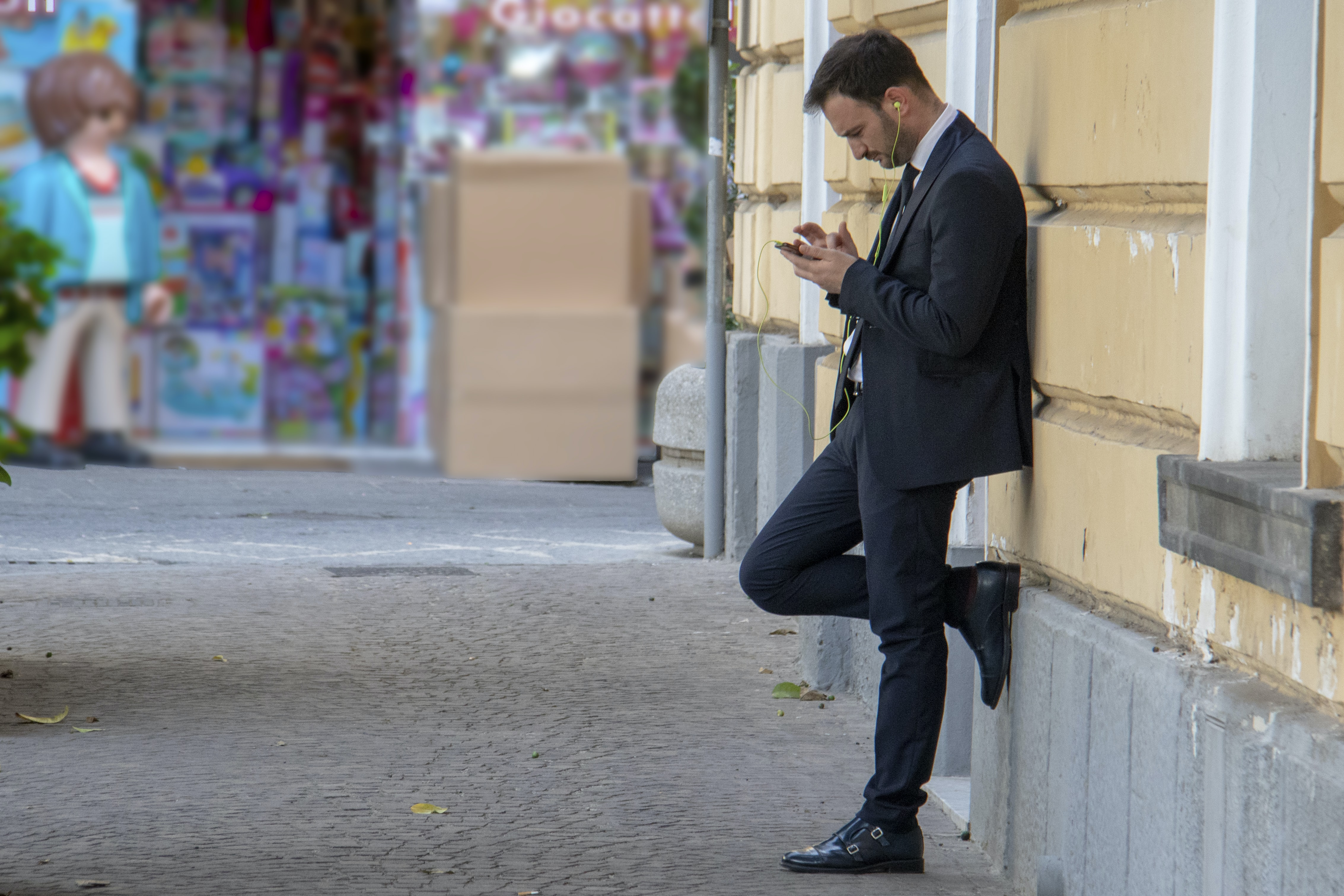 man holding his phone while leaning on building