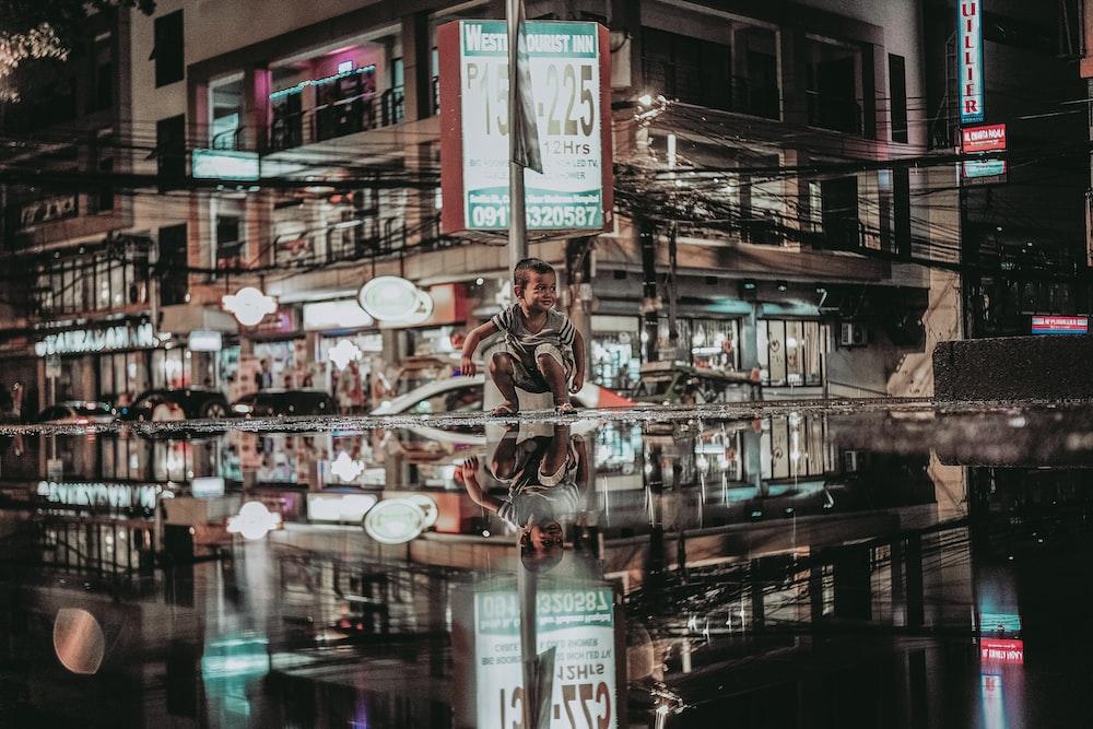 reflection photography of boy sitting beside pole near restaurant