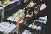 person taking photo of assorted vinyl album