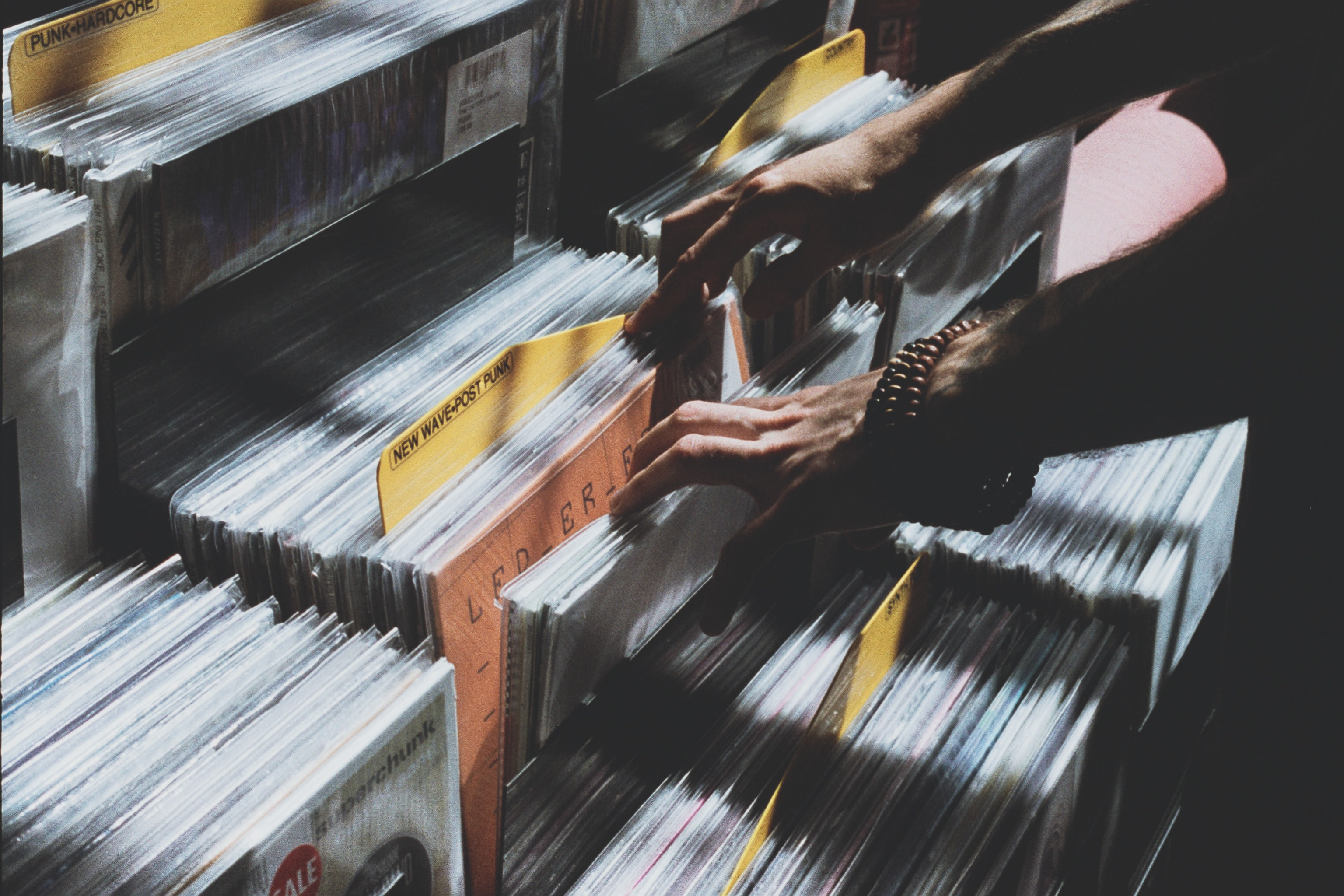 person taking photo of assorted vinyl album