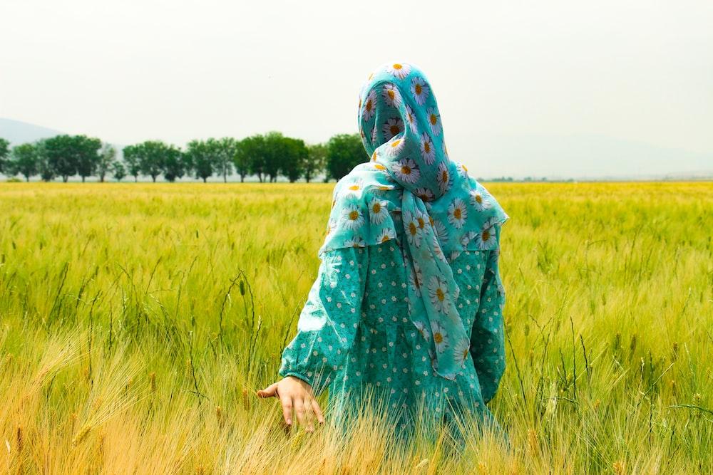 woman walking on green grass field