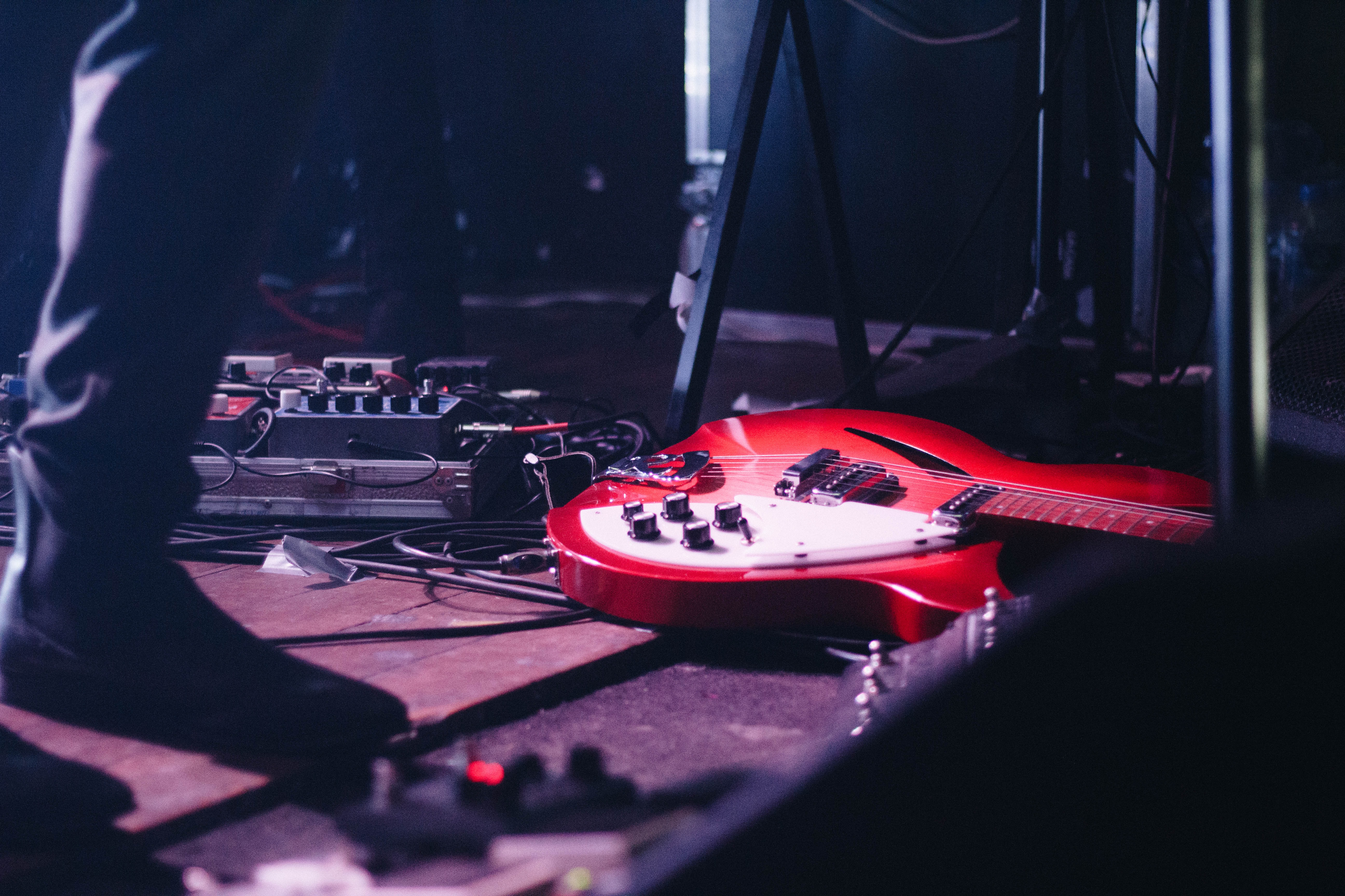 red electric guitar on flooring