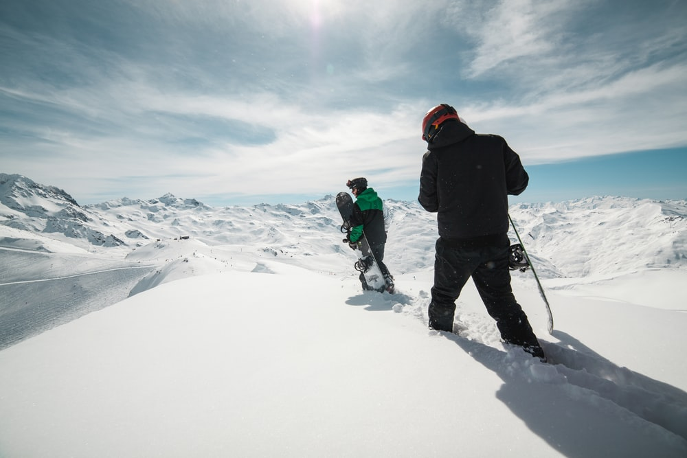 two people carrying snowboards on snow covered terrain